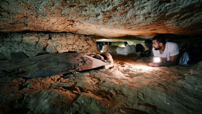 Arqueólogo observa tumba em Menia, no Egito