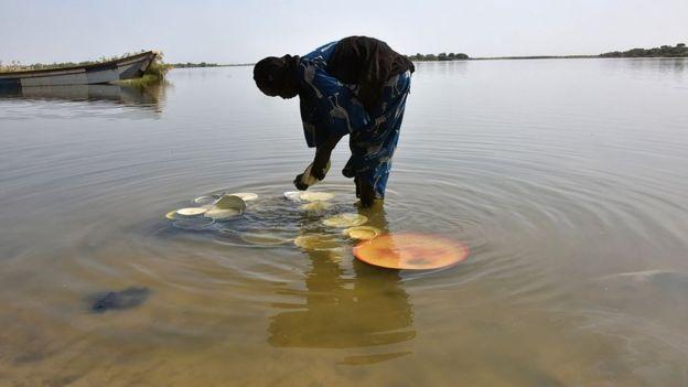 Mulher lava prato no lago Chade