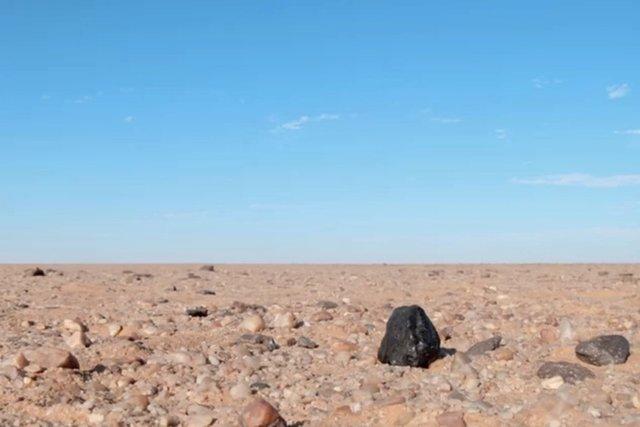 """A """"rocha"""" negra é um meteorito Almahata Sitta encontrado no deserto da Núbia, no norte do Sudão."""